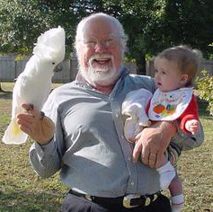image of Jerome Bump holding a very small child in one hand and a large cockatoo in the other